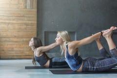 Le giovani donne nell'yoga classificano, piegano l'allungamento di posa Immagini Stock