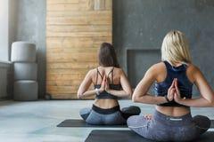Le giovani donne nell'yoga classificano, posa inversa di preghiera Fotografia Stock