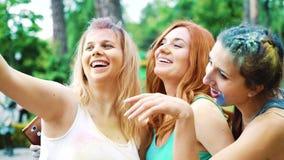 Le giovani donne ridono della macchina fotografica e fanno i selfies dopo il festival di colori di Holi stock footage