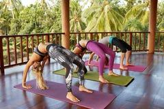 Le giovani donne in ruota flessibile posano alla classe di yoga Immagine Stock