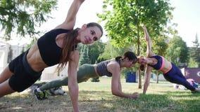 Le giovani donne si esercitano fisici sull'erba nel parco, di estate stock footage