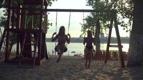 Le giovani donne si rilassano sull'oscillazione alla spiaggia video d archivio