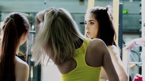 Le giovani donne snelle incantanti stanno parlando dopo un allenamento del gruppo stock footage