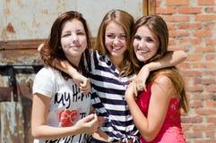 Le giovani donne sorridenti & di sguardi felici della macchina fotografica si divertono in città all'aperto Fotografie Stock Libere da Diritti