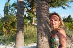 Le giovani donne sta levandosi in piedi vicino alla palma Fotografie Stock Libere da Diritti