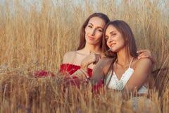 Le giovani donne stanno sedendo nell'erba alta Fotografia Stock Libera da Diritti