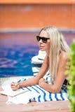 Le giovani free lance bionde della ragazza in bikini lavorano vicino alla piscina, immagini stock