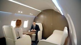 Le giovani persone di affari stanno discutendo l'affare moderno, sedentesi in aereo privato archivi video