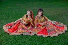Le giovani ragazze sorridenti indiane si siedono su erba immagini stock libere da diritti