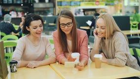 Le giovani signore allegre stanno utilizzando lo smartphone che esamina insieme lo schermo che sorridono e la seduta di risata in video d archivio