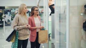 Le giovani signore attraenti stanno chiacchierando in centro commerciale moderno che camminano lungo le finestre poi che esaminan stock footage