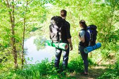 Le giovani viandanti delle coppie in foresta mette in mostra l'uomo e la donna con gli zainhi sulla strada in natura fotografia stock