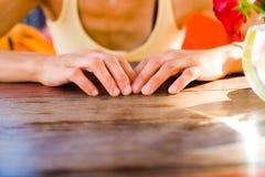 Le girl& x27 ; les mains de s sont sur la table Photos libres de droits