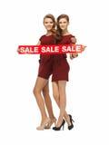 Le girsl adolescent en rouge s'habille avec le signe de vente Photos stock