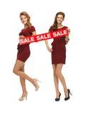 Le girsl adolescent en rouge s'habille avec le signe de vente Images stock