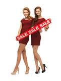 Le girsl adolescent en rouge s'habille avec le signe de vente Photographie stock libre de droits