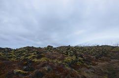 Le gisement de lave avec de la glace a couvert des montagnes à l'arrière-plan photos libres de droits