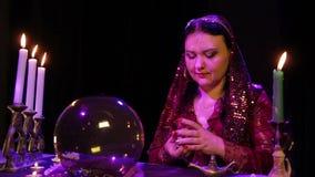 Le gitan dans une robe rouge dans la fumée par lueur d'une bougie bat des cartes pour la divination banque de vidéos