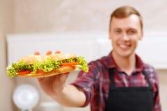 Le gjorda smörgåsen för man den visning Royaltyfri Bild