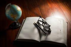 Le globe avec des lunettes, le stylo et le plan réservent Photographie stock