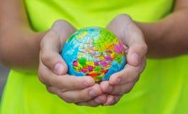Le globe bleu dans des mains avec les territoires des pays du monde sur un fond vert image libre de droits