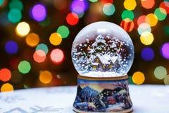 Le globe de neige de Noël devant l'arbre de Noël allume le plan rapproché Photographie stock