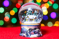 Le globe de neige de Noël devant l'arbre de Noël allume le plan rapproché Photo stock
