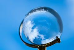 Le globe en verre sur un fond de ciel bleu Images stock