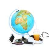 Le globe, le téléphone, les lunettes de soleil et les écouteurs bleus sur le fond blanc Image stock