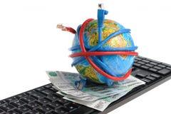 Le globe a lové les fils, billets de banque sur le clavier Photos libres de droits