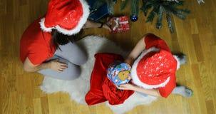 Le Gnome retire des cadeaux du sac, et la jeune fille de neige les met sous l'arbre banque de vidéos