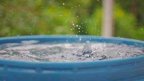 Le gocce dell'acqua dal tetto cadono in un barilotto blu archivi video