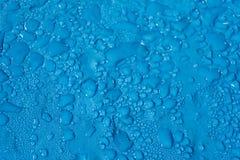 Le gocce di acqua delle dimensioni differenti su un blu liscio sorgono immagine stock libera da diritti