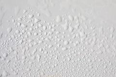 Le gocce di acqua si chiudono su sul bordo bianco immagini stock