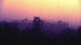 Le gocce di pioggia colpiscono il vetro di finestra archivi video
