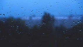 Le gocce di pioggia colpiscono il vetro di finestra video d archivio