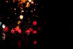 Le gocce di pioggia d'ardore astratte di alta risoluzione eccellenti hanno offuscato il fondo nello scuro Fotografia Stock