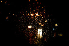 Le gocce di pioggia d'ardore astratte di alta risoluzione eccellenti hanno offuscato il fondo nello scuro Fotografie Stock Libere da Diritti
