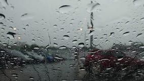 Le gocce di pioggia scorrono giù il parabrezza Vista dall'interno dell'automobile Sulla via esegue un uomo bagnato video d archivio