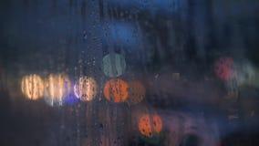 Le gocce di pioggia sul vetro di finestra dell'automobile con l'automobile vaga della città di notte accende Bokeh come fondo 4K stock footage