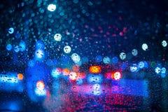 Le gocce di pioggia sulla finestra con la strada accendono il bokeh che piove la stagione immagine stock libera da diritti