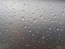 Le gocce di pioggia sulla superficie dell'automobile o sulla superficie del ferro scorrono giù Immagine Stock