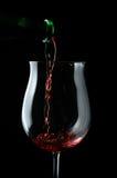 Le gocce rosse wine essendo versando in un vetro di vino immagini stock libere da diritti