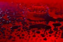 Le gocce, spruzza, spruzza dell'acqua su un fondo variopinto fotografia stock