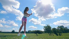 Le golfeur féminin frappe une boule, se tenant sur un champ Le golfeur joue au golf, concept de mode de vie de sport banque de vidéos
