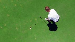 Le golfeur frappe une boule dans un trou sur un champ jouant au golf clips vidéos