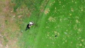 Le golfeur joue sur un cours vert banque de vidéos