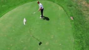 Le golfeur masculin met la boule blanche dans un trou sur un champ clips vidéos
