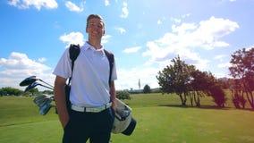Le golfeur masculin se tient sur le champ et le sourire banque de vidéos