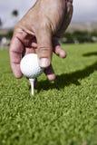 Le golfeur place la bille de golf sur le té images stock